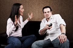 Couch potato and angry wife. Angry wife yelling at couch potatoe husband stock image