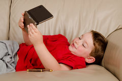 Couch potato concept of boy playing video game Stock Photo