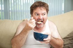 Couch Potato Eating Cereal. Unemployed man sitting on the couch eating cereal as he watches television stock photos