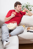 Couch potato eating junk food. During watching tv Royalty Free Stock Photos