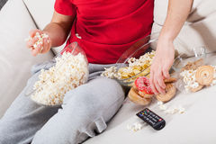 Couch potato watching tv. And eating junk food Stock Photos