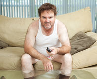 Couch Potato Watching TV. Unemployed man sitting home watching TV, bored and discouraged stock photography