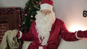 Santa Claus with an empty bag. On the couch sat Santa Claus and examines an empty bag for gifts stock video