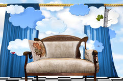 Couch on stage set. A tan couch on a conceptual stage set with curtains and clouds.  Concept for story time and imagination.  This couch or settee is a place for Stock Photo