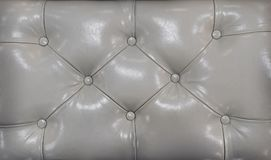 Couch-type screed. Retro light coloured chesterfield style quilted upholstery backdrop close up. Beige capitone pattern. Couch-type screed. Retro dark Stock Photography