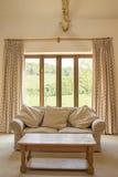 Couch und Couchtisch vor Terrassentüren lizenzfreie stockbilder