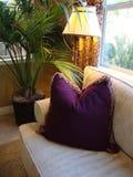 Couch und purpurrotes Kissen Stockfotos