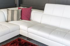 Couch with white upholstery and two pillows Stock Images