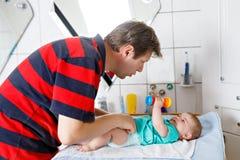 Couche-culotte changeante de père affectueux de sa fille nouveau-née de bébé image libre de droits