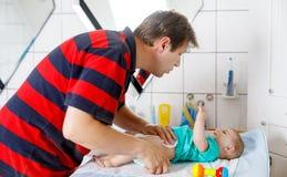 Couche-culotte changeante de père affectueux de sa fille nouveau-née de bébé photos libres de droits