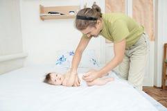 Couche-culotte changeante de papa sur le bébé sur le lit, couche changeante, vie quotidienne photo libre de droits