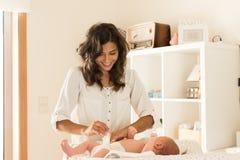 Couche-culotte changeante du ` s de bébé de mère images stock