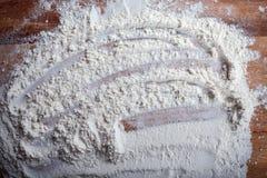 Couche de farine avec le modèle chaotique sur la planche à découper Photos stock