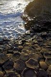 Coucher de soleil accentuant les dalles hexagonales de basalte de la chaussée de Giants Image stock