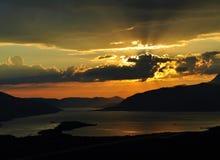 Coucher du soleil à la baie de Kotor avec le soleil brillant derrière les nuages Image stock