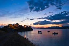 Coucher du soleil à la baie de Toroni avec la vieille forteresse romaine, les bateaux de pêche et quelques îles à un arrière-plan Images libres de droits