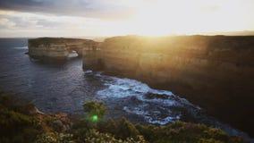 Coucher du soleil à la falaise de mer de roche le long de la grande route d'océan banque de vidéos