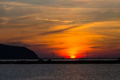 Coucher du soleil à la lagune de lefkas en Grèce avec la digue, l'eau, réverbères Image stock