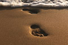 Coucher du soleil à la mer Empreintes de pas dans le sable La mer, égalisant Calmez vers le bas Reste sur la mer Images stock