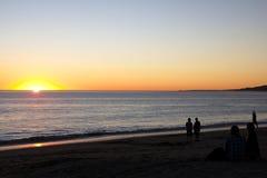 Coucher du soleil à la plage avec l'observation de personnes Photographie stock libre de droits