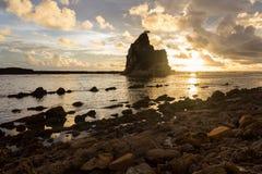 Coucher du soleil à la plage de Sawarna avec le ciel lumineux d'or Photographie stock libre de droits