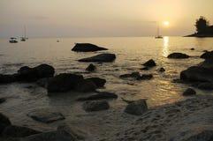 Coucher du soleil à Phuket sur une mer d'or calme avec des bateaux et des roches Photographie stock