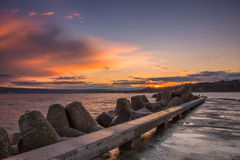 Coucher du soleil à une jetée de mer Photos libres de droits