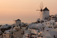 Coucher du soleil étonnant au-dessus des moulins à vent blancs dans la ville d'Oia et de panorama vers l'île de Santorini, Cyclad Photo libre de droits