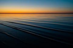Coucher du soleil étonnant vif dans les pays Baltes - le crépuscule en mer avec l'horizon illumine par le soleil photographie stock libre de droits