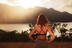 Coucher du soleil admiratif de jeune femme au-dessus de baie Photos libres de droits