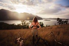 Coucher du soleil admiratif de jeune femme au-dessus de baie Images stock