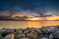Coucher du soleil ardent derrière le rivage rocheux Photos libres de droits