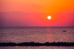 Coucher du soleil au bord de la mer avec le bateau et la mer Photo libre de droits