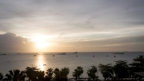 Coucher du soleil au-dessus d'océan avec les palmiers silhouettés Image stock