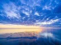 Coucher du soleil au-dessus d'océan - ciel nuageux bleu, soleil, et eau lisse photographie stock libre de droits