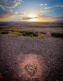 Coucher du soleil au-dessus d'un coeur fait de cailloux Photographie stock
