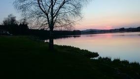 Coucher du soleil au-dessus d'un lac avec des montagnes à l'arrière-plan Photo libre de droits