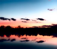 Coucher du soleil au-dessus d'un lac avec des réflexions dans l'eau photographie stock libre de droits