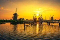 Coucher du soleil au-dessus d'un pont-levis historique et de vieux moulins à vent dans Kinderdijk, Pays-Bas Photo libre de droits