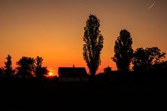 Coucher du soleil au-dessus d'une maison du comté Image libre de droits