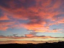Coucher du soleil au-dessus d'une montagne silhouettée images stock