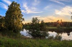 Coucher du soleil au-dessus d'une petite rivière russe Photographie stock libre de droits