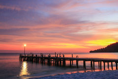 Coucher du soleil au-dessus d'une plage et d'un pilier en bois Images stock