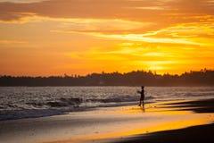 Coucher du soleil au-dessus d'une plage tropicale avec la silhouette d'un pêcheur de garçon Photographie stock libre de droits