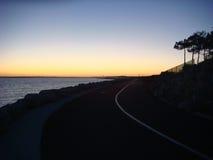 Coucher du soleil au-dessus d'une route par la mer Photographie stock libre de droits