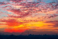 Coucher du soleil au-dessus d'une ville industrielle Photos stock