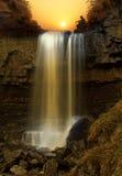 Coucher du soleil au-dessus de cascade à écriture ligne par ligne Image libre de droits