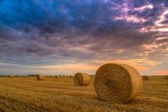 Coucher du soleil au-dessus de champ de ferme avec des balles de foin Photo stock