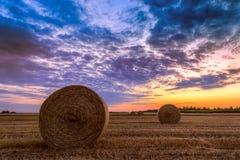 Coucher du soleil au-dessus de champ de ferme avec des balles de foin Photo libre de droits