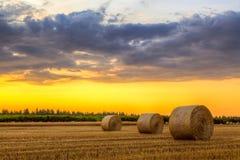 Coucher du soleil au-dessus de champ de ferme avec des balles de foin Image stock